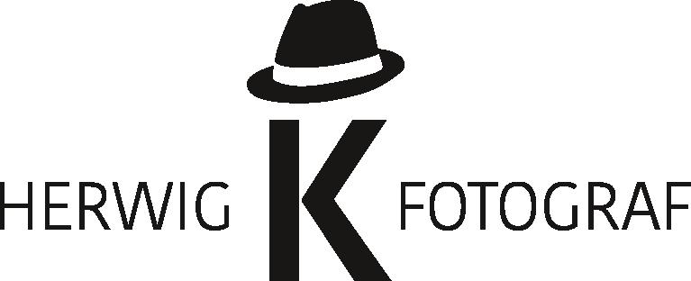 Logo des Fotografen Herwig Korbel. Schwarzer Schriftzug, alles in Großbuchstaben: Herwig K Fotograf. Wobei das K deutlich größer ist als der Rest der Schrift. Das K trägt einen schwarzen Hut. Eine Idee der Grafikerin Marlene Böhm, der aufgefallen ist, dass Herwig sehr häufig Hüte trägt.
